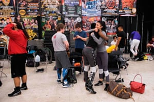 As the male counterparts gather after a training session, Gia Scott (fourth from left) gets a hug from training partner and former WWE female wrestler Rosa Mendes during a class in Joppa, Maryland.