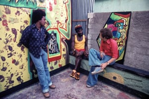 Lee 'Scratch' Perry (centre) is interviewed by director Jeremy Marre (right) with a local film crew member on the left, in front of mural on the side of Perry's Black Ark studio in Kingston, Jamaica, during the making of Harcourt Film Roots Rock Reggae in 1977.
