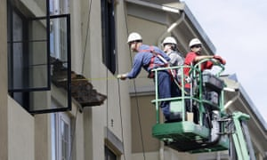 A worker measures near the remaining wood from an apartment building balcony that collapsed in Berkeley, California, killing six people.