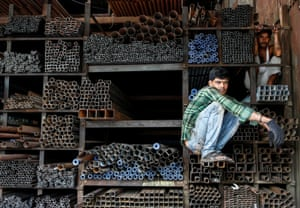 Labourers wait to load metal pipes inside a shop in Mumbai, India