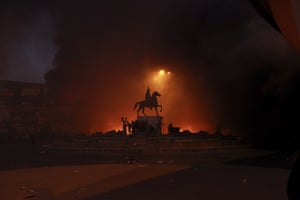 Anti-government protestors start fires while security forces fire teargas in Baghdad.