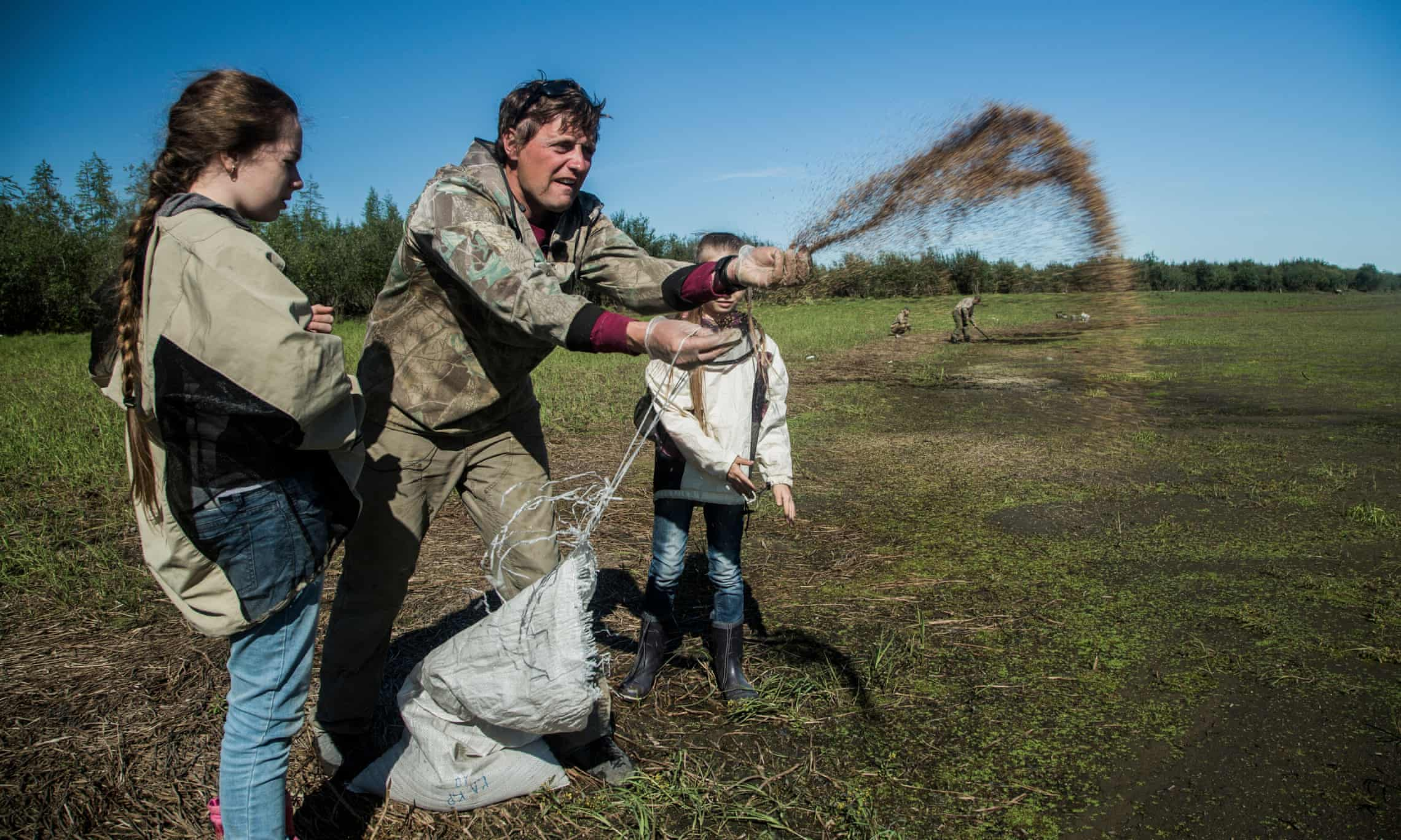 Nikita Zimov and his daughters plant grass seeds at Pleistocene Park near Cherskiy, Siberia, as part of a new experiment to prevent permafrost thaw by breaking up the snow that would otherwise insulate it against cold. Photograph: Katie Orlinsky