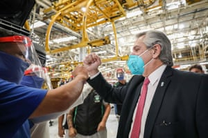 The Argentine president, Alberto Fernandez, greets a worker at a Volkswagen factory in Buenos Aires after it restarted production