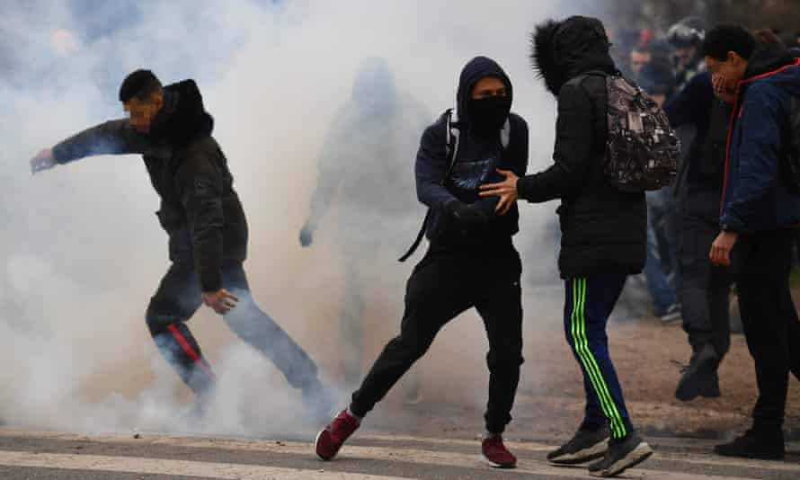 """People run away from tear gas launched by riot police during a protest of students against police brutality, following the alleged rape of Theo, next to the """"ycee Voltaire secondary school in Paris."""