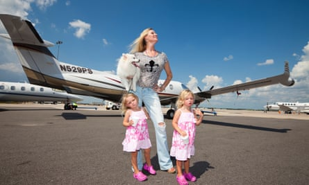 Jackie Siegel, aka the Queen of Versailles, with her twin girls in front of their private plane in Orlando, Florida.