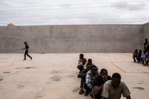 African migrants have their lunch break in the courtyard of the Karareem detention centre near Misrata, Libya