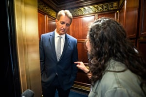 A protester confronts Senator Jeff Flake in a lift after he announces he is voting to confirm Brett Kavanaugh's nomination.