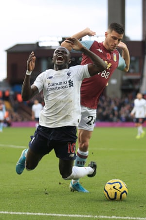 Liverpool's Sadio Mane goes down under a challenge from Aston Villa's Frederic Guilbert, but is then booked for diving. Mane scored the winner in injury time to make it 1-2 and seal the points for the league leaders at Villa Park.