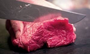 Meat being cut on a chopping board