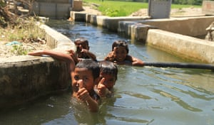 Children play in the irrigation channels near a dam in the special economic zone of Oecusse