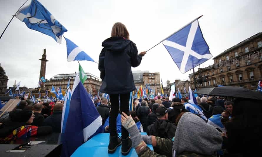 Eight-year-old Erin Burns, from Partick, waves a Scottish saltire flag while her mum, Katy Burns, steadies her at a Scottish independence rally in Glasgow on 2 November 2019.