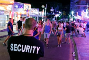 A security worker looks at tourists walking at Punta Ballena street in Magaluf,