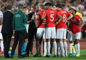 The England players and manager Gareth Southgate speak to referee Ivan Bebek as the match is stopped during the first half.