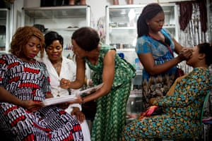 An apprentice hairdresser at the Jumelle salon in Conakry shows a client different family planning methods