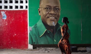 A woman walks past an election billboard after John Magufuli (pictured on billboard) was named president-elect