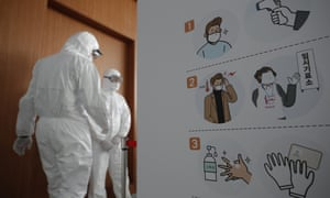 Workers wearing protective gear stand near a banner ahead of the early voting for the upcoming Seoul mayoral by-election at a local polling station in Seoul, South Korea, Thursday, April 1, 2021.