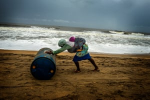 A woman carries her baby on her back as she pushes 200 litres of smuggled gasoline along the beach in Aného