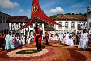 People walk over a sawdust carpet under a big red banner