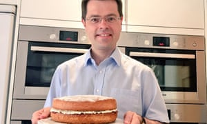 James Brokenshire holds a cake in front of his four ovens