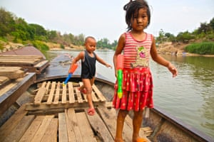 Two children play with water pistols in a boat near the Thai-Myanmar border