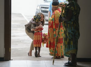 The first lady embraces a flower girl as she arrives at the Emintsimadze Palace in Ghana to meet chieftains of the Cape Coast Fante.