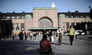 A homeless woman sits outside downtown Helsinki central station in 2011.