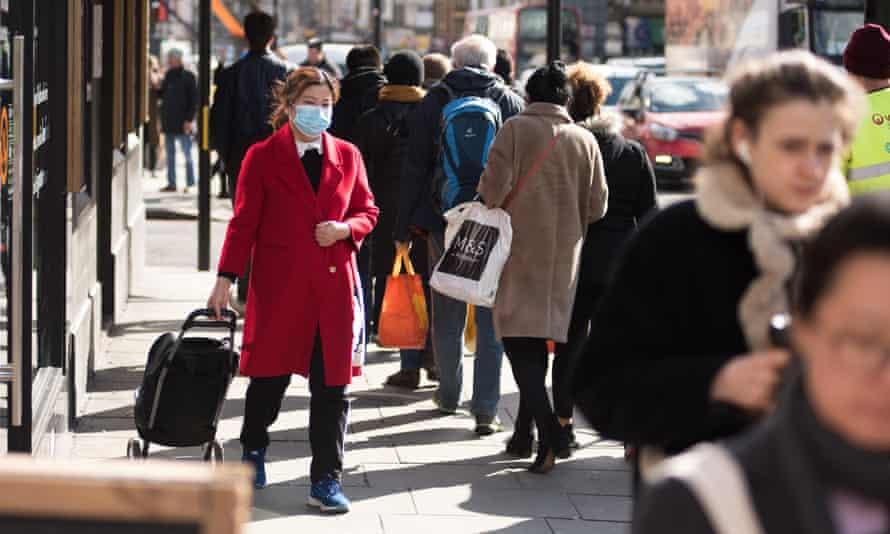 A woman wears a face mask as she walks along Camden Town high street in London
