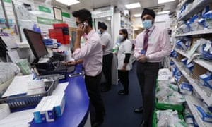 Pharmacists working wearing facemasks.