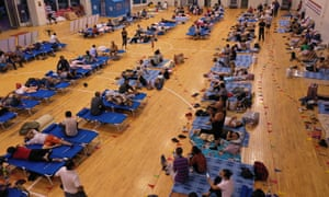 People take refuge in a stadium serving as temporary shelter during Typhoon Lekima