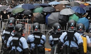 Policemen in anti-riot gear stand watch as protesters use umbrellas to shield themselves near the Legislative Council in Hong Kong.