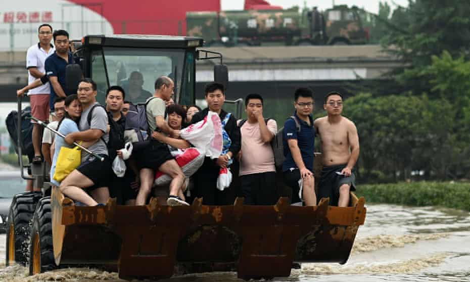 People ride in the front of a loader to cross a flooded street in Zhengzhou, Henan province