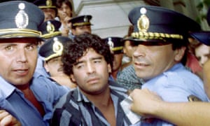 Diego Maradona escorted by police as he leaves a courthouse after answering charges he shot and injured journalists, March 1994.