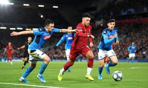 Alex Oxlade-Chamberlain of Liverpool runs with the ball under pressure from Napoli's Mario Rui and Eljif Elmas.