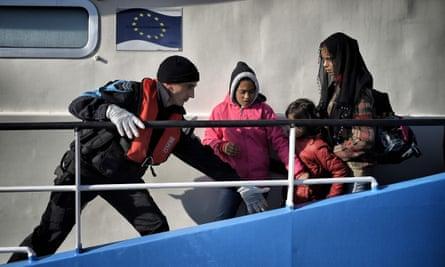 A coastguard helps children disembark from a Frontex ship