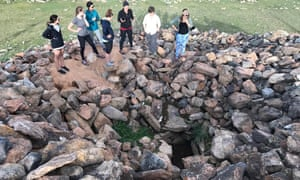 Archaeologists and Cultural Heritage Director at the American Center for Mongolian Studies, Dr. Julia Clark, shows a newly looted burial to a group of archaeology students in July, 2017.