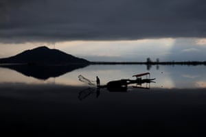 A fisherman casts a net in the waters of Dal Lake with clouds in the background, Srinagar