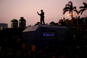 Jakarta, Indonesia: A police officer holds a phone at a protest outside the Indonesian Parliament