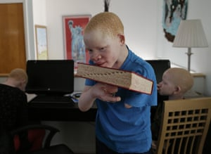 Emmanuel Festo Rutema, 13, carries a dictionary back to a shelf during his lesson with Mwigulu in Staten Island.