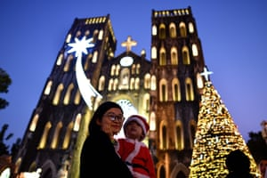 A woman carries her child dressed in Santa Claus costume as they walk past the late 19th-century St Joseph's cathedral
