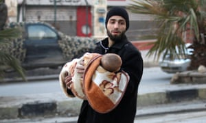A man carries a child as he flees deeper into the remaining rebel-held areas of Aleppo, Syria.