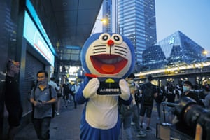 "A demonstrator dressed as cartoon character Doraemon holds a placard reading ""People wishes can come true"" on Friday."