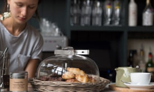 Waitress behind the counter at Bistro Lotte, Frome, Somerset, UK. On the counter are pastries and coffee cups.