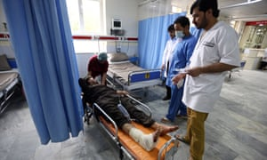 Afghan health workers tend to a man injured in the attack in Kabul on Tuesday