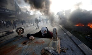 A Palestinian protester takes cover during clashes with Israeli troops in Beit El, near Ramallah.