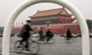 Chinese cyclists pedal past the Forbidden City in Beijing.