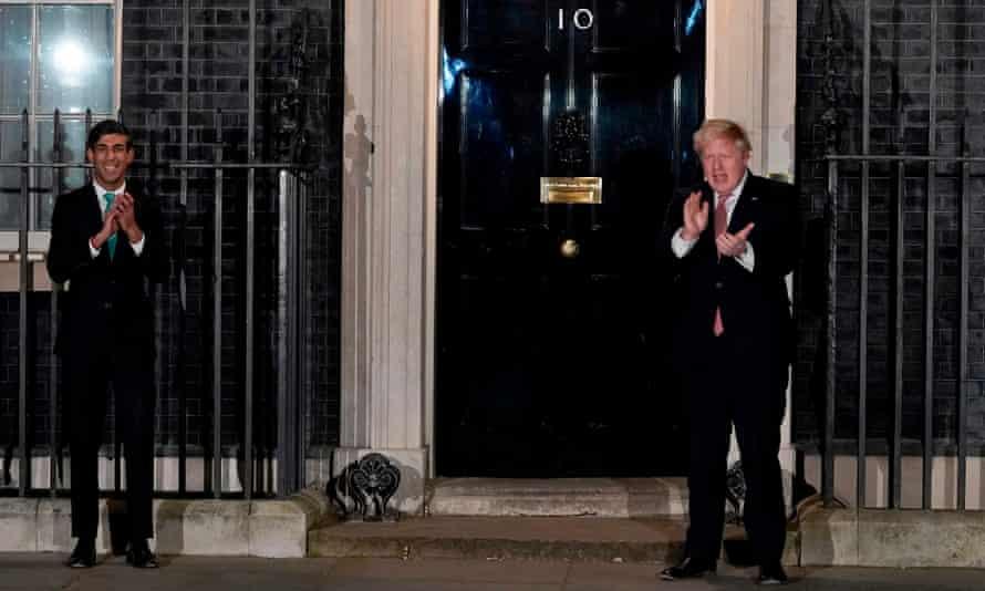 Boris Johnson (R) and Rishi Sunak clap in appreciation of NHS workers.