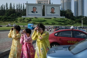 Women in traditional dress shield their faces from the sun as they cross a street in Pyongyang.