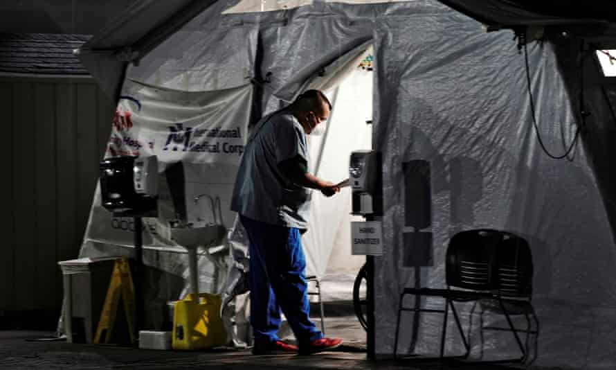 A healthcare worker checks on patients inside an oxygen tent outside the emergency room in Huntington Park, California, on 29 December 2020.