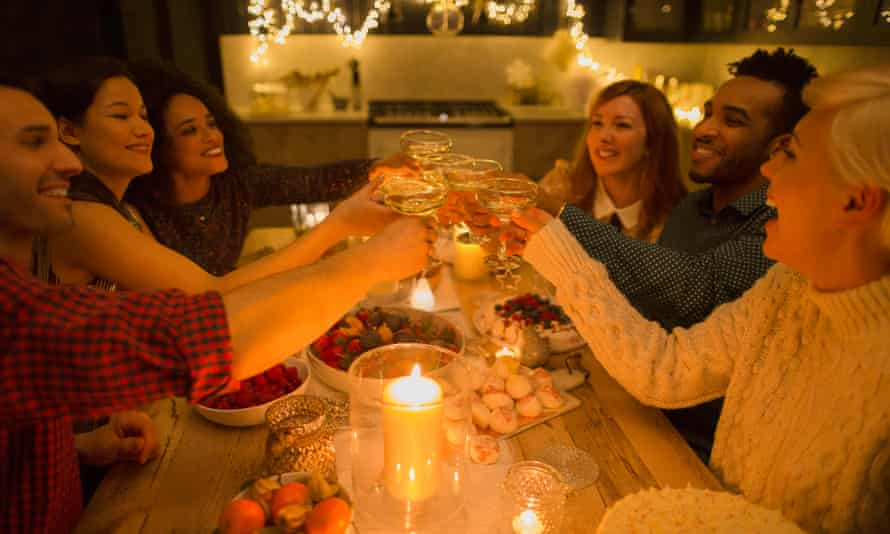 Friends toasting champagne glasses at candlelight table