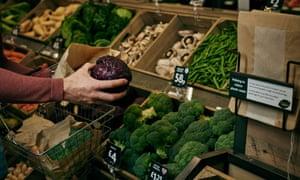 Shopper choosing vegetables in Morrisons with paper bags on display